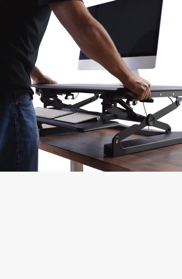 A man adjusts a standing desk converter