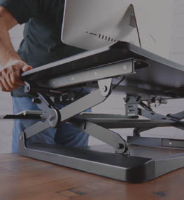 man adjusts a standing desk converter with ease