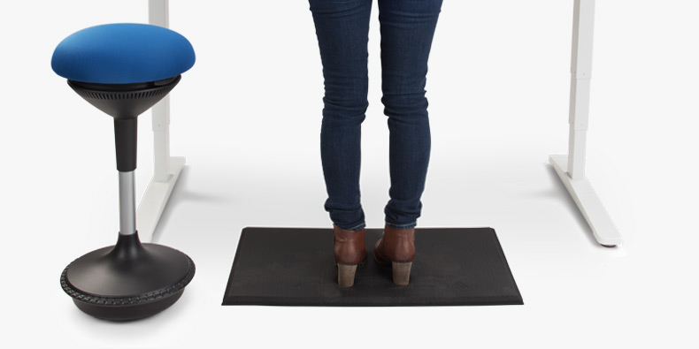 a woman tasks in comfort while standing on an antifatigue standing desk mat at